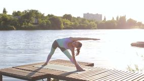 Flexible girl doing yoga exercise on a pier. Happy smiling girl doing yoga on a wooden bridge near the shore of the lake. Morning work-out outdoors, sports and stock video