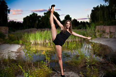flexible girl holding leg up against pond Royalty Free Stock Images