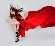 Flexible girl moves in a red long dress Stock Images