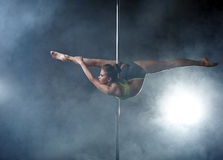 Flexible girl posing in difficult position on pole Stock Images