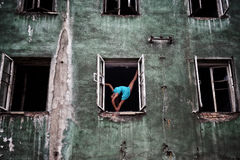Flexible girl standing in a ballet pose in the opening windows on the facade of an old abandoned building Royalty Free Stock Photo