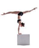 Flexible gymnast balancing on cube in studio Royalty Free Stock Images