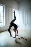 Flexible gymnast doing exercise Stock Image