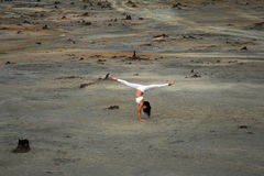Flexible gymnast girl in a beautiful pose on a background of apocalyptic landscape in the desert Stock Photos