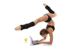 Flexible gymnast with laptop and apple Royalty Free Stock Photography
