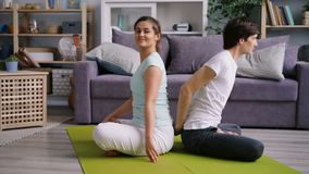 Flexible husband and wife exercising at home together doing yoga for couples