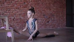 Flexible Jugendliche, die in ein Studio in der Front die Backsteinmauer ausdehnend aufwärmt Beinspalte lehnt Vorderbein auf einem stock video footage