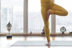 Flexible junge Frau, die Yoga in der Wohnung tut stockfotografie