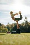 Flexible junge Paare, die draußen acroyoga tun Stockfoto