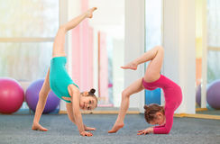 Flexible kids gymnasts doing acrobatic exercise in gym. Sport concept. Flexible kids gymnasts doing acrobatic exercise in gym. Sport, training, fitness, yoga Stock Photography