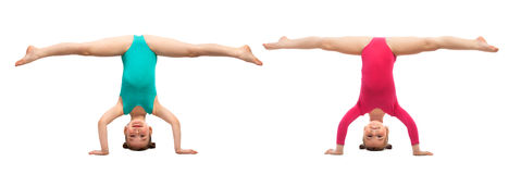Flexible kids gymnasts standing on head, isolated white background Stock Image