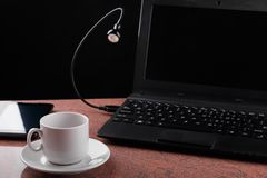 LED USB lamp connected to laptop and looking at coffee cup. Concept of alive usb-lamp. Black background. Flexible LED USB lamp connected to laptop and looking at royalty free stock photography