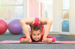 Flexible little girl gymnast doing acrobatic exercise in gym Stock Image