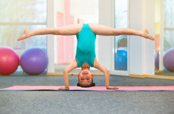 Flexible little girl gymnast standing on head in gym stock image