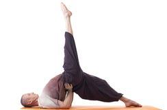 Flexible man practicing yoga exercises in studio Royalty Free Stock Image
