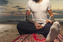 Flexible man with tattoo doing yoga lotus pose Royalty Free Stock Image