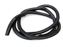 Flexible pipe. Coil of black flexible plastic corrugated pipe isolated on the white background. Cable protection Royalty Free Stock Photography