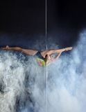 Flexible pole dancer performs acrobatic pas Royalty Free Stock Images