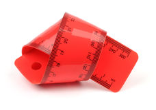 Flexible Ruler. Twisted red plastic ruler on white background Stock Photos