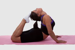 Flexible woman. Young brunette woman wearing workout clothes doing yoga stretch on pink mat stock photos