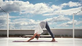 Flexible woman does yoga in slow motion in background of clouds and blue sky. Flexible woman does yoga in slow motion in background of white clouds and bright stock video