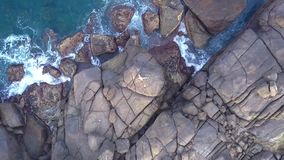 Flexible woman lies on huge grey stone by turquoise ocean. Camera zooms out flexible woman lying on huge grey stone with green bushes by turquoise ocean bird eye stock video