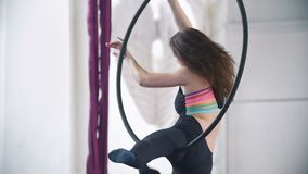 Flexible woman makes a gymnastic elements on the aerial hoop. Slow motion stock video footage