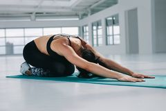Flexible woman performing yoga. At fitness studio. Healthy woman exercising on yoga mat bending over with arms stretched in front at gym Stock Image