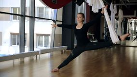 Flexible woman performs stretching of limbs with support on white air cloth. During yoga classes female person in black elastic suit makes a gymnastic twine in stock footage