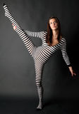 Flexible Woman in Striped Bodysuit Royalty Free Stock Photos