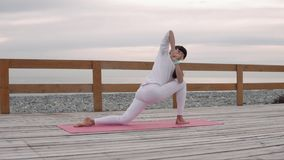 Adult woman practicing yoga at sea. stock video
