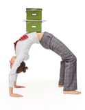 Flexible workflow. Business woman in flexible pose (bridge pose) with boxes with documant on top Royalty Free Stock Photo