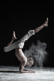 Flexible yoga man doing hand balance asana vrischikasana. Dust flying in air stock image