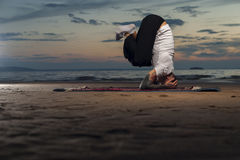 Flexible yoga man doing head stand on the beach Royalty Free Stock Photo