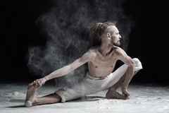 Flexible yoga man doung wide side lunge or utthita namaskarasana. Dust flying in air. aghori concept Royalty Free Stock Images