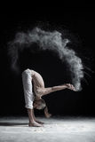 Flexible yoga man in standing forward fold uttanasana. Dust flying in air. aghori concept Royalty Free Stock Photo