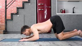 Flexible yogi male practicing cobra position on mat at home kitchen side view stock video footage
