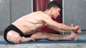 Flexible yogi man enjoying training making stretching exercise on mat side view stock video