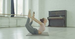 Flexible yogi woman stretching in bow pose exercise. Flexible graceful woman with perfect body practicing yoga, stretching in dhanurasana exercise, bow pose on stock video footage