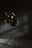 Flexible young dancer performing in the air. Full of expressiveness . Charismatic flexible expressive man dancing in the dark lighted room and stretching while Royalty Free Stock Photos