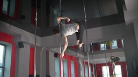 Flexible young man exercising pole dance elements on a pole. Slow motion stock video