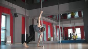 Flexible young man performing pole dance elements on a pole. Slow motion stock video footage