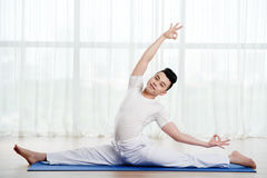Flexible young man. Smiling handsome Asian man doing splits on yoga mat Royalty Free Stock Photos