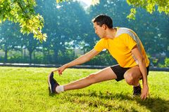 Flexible young man stretching legs outdoors Royalty Free Stock Photography