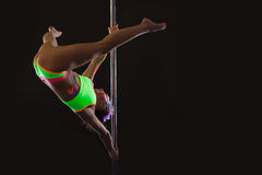 Flexible young pole dancer exercising stretching Stock Images