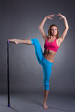 Flexible young sportswoman posing in studio Royalty Free Stock Images