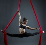 Flexible young woman dancing using hanging ribbons Stock Image
