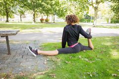 Flexible young woman doing the splits exercise in park. Rear view of a flexible young woman doing the splits exercise in the park Royalty Free Stock Photography