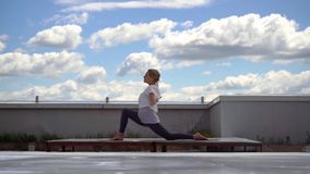Flexible young woman doing yoga warrior pose with knee support in slow motion. Girl doing stretching yoga exercise in background of white clouds and bright stock video