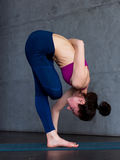 Flexible young woman performing one-leg balance exercise doing half bound lotus standing forward fold pose indoors Royalty Free Stock Photo